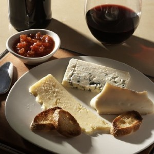 Glass of red wine with a plate of cheese and a small bowl of chutney