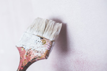 Paint brush on white wall